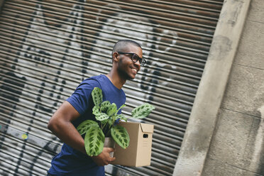 Portrait of happy young man carrying cardboard box and foliage plant - EBSF000818
