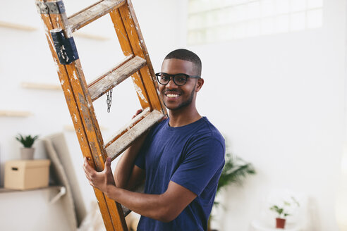 Portrait of smiling young man with ladder in his new flat - EBSF000819