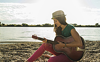 Young woman playing guitar by the riverside - UUF005000