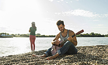 Young man playing guitar with woman by the riverside - UUF005002