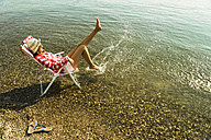 Young woman sitting on deckchair in river splashing with water - UUF005023