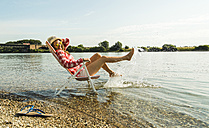 Young woman sitting on deckchair in river splashing with water - UUF005025