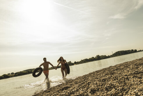 Young couple running with inner tubes in river - UUF005033