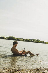 Young man sitting in inner tube in river using smartphone - UUF005039