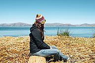Peru, Puno, woman wearing chullo sitting on floating island in Lake Titicaca - GEMF000289