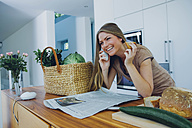 Happy woman on phone in kitchen taking groceries from bag - CHAF000838