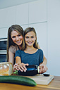 Mother and daughter in kitchen preparing healthy food - CHAF000841
