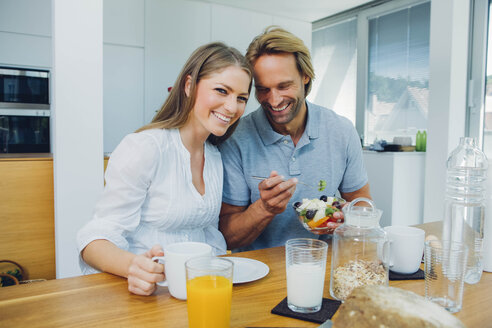 Happy couple eating at kitchen table - CHAF000860