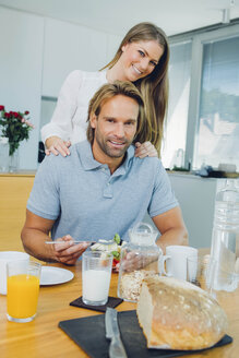 Portrait of couple eating at kitchen table - CHAF000863