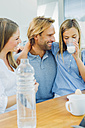Happy mother and father looking at daughter drinking milk - CHAF000871
