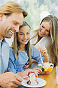 Happy mother, father and daughter eating at table - CHAF000873