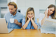 Frustrated girl with distracted parents at table - CHAF000969