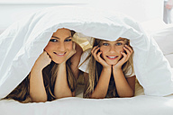 Happy mother and daughter under blanket - CHAF000876