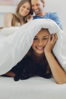 Portrait of happy girl with puppy in bed and parents in background - CHAF000973