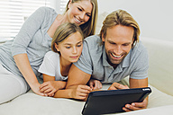 Happy father, mother and daughter lying on couch sharing digital tablet - CHAF000882