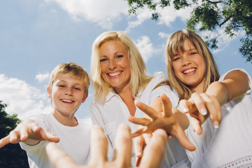 Portrait of happy mother with her children reaching for photographer's hand - CHAF001564