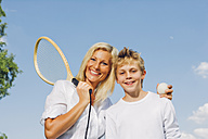 Portrait of happy mother and son with tennis racket and ball against blue sky - CHAF000912