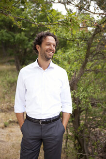 Germany, smiling businessman in forest - MFRF000246