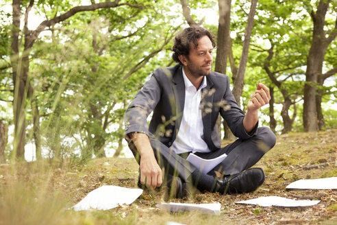 Germany, businessman sitting in forest looking at leaf - MFRF000249