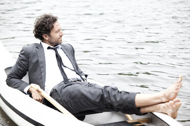 Germany, Rur Reservoir, businessman relaxing in canoe - MFRF000255