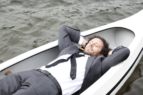 Germany, Rur Reservoir, businessman sleeping in canoe - MFRF000257