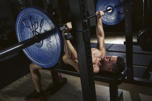 Physical athlete doing barbell bench presses - MADF000434