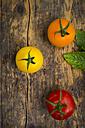 Three different tomatoes on wood - LVF003712