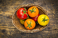 Wickerbasket of different tomatoes on wood - LVF003715