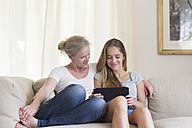 Mother and daughter sitting with digital tablet  on the couch - SGF001795