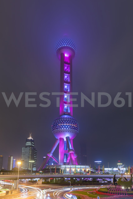 China, Shanghai, Oriental Pearl Tower sticking in low clouds at night - NKF000327