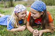 Two little sisters with headscarfs lying on a meadow - MGOF000350