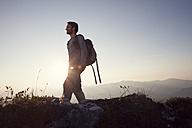 Austria, Tyrol, man hiking at Unterberghorn at sunset - RBF002928