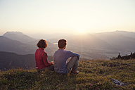 Austria, Tyrol, Unterberghorn, two hikers resting in alpine landscape at sunset - RBF002942