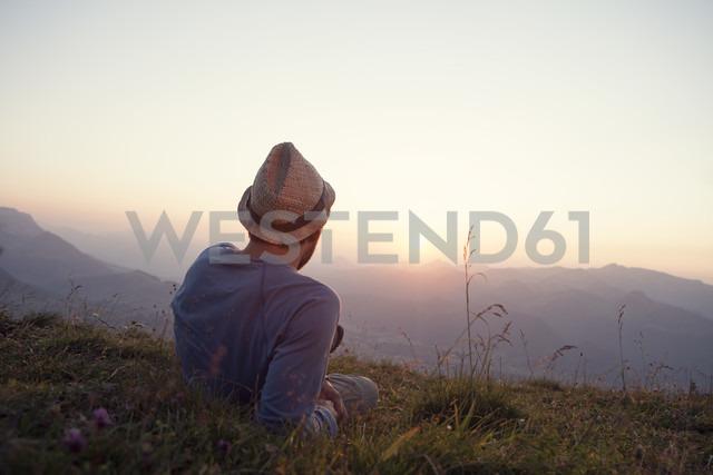 Austria, Tyrol, Unterberghorn, man resting on alpine meadow at sunset - RBF002948