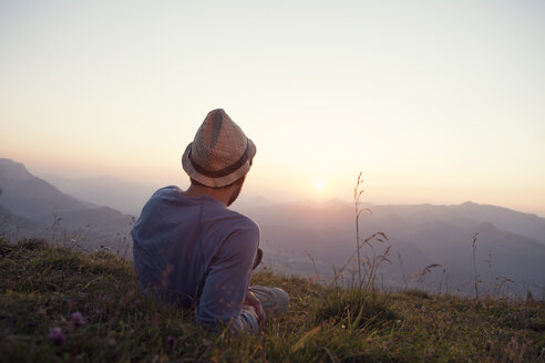 Austria, Tyrol, Unterberghorn, man resting on alpine meadow at sunset - RBF002948