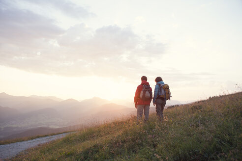 Austria, Tyrol, couple hiking at Unterberghorn at sunrise - RBF002953