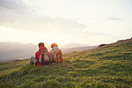 Austria, Tyrol, Unterberghorn, two hikers resting in alpine landscape at sunrise - RBF002957
