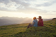 Austria, Tyrol, Unterberghorn, two hikers resting in alpine landscape at sunrise - RBF002962