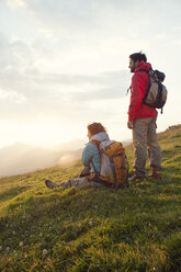 Austria, Tyrol, Unterberghorn, two hikers resting in alpine landscape at sunrise - RBF002966