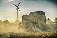 Germany, Grevenbroich, combine harvester on field and wind turbine - FR000292