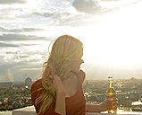 Germany, Berlin, young woman with beverage looking at view - BFRF001402