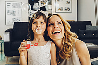 Happy mother with daughter at home blowing soap bubbles - CHAF000987