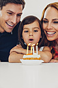 Family with daughter celebrating birthday with candles on cake - CHAF000990