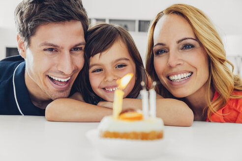 Family with daughter celebrating birthday with candles on cake - CHAF000993