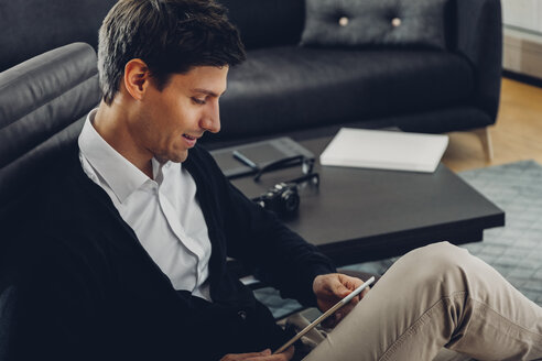 Young man in living room using digital tablet - CHAF000934
