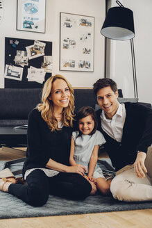 Happy family with daughter sitting on floor in living room - CHAF000996