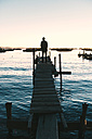 Bolivia, Man standing on wooden boardwalk looking the Titicaca Lake at sunset - GEMF000293
