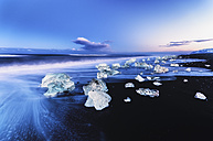 Iceland, view to glacial lake Jokulsarlon, glacier ice on beach at twilight - SMA000354