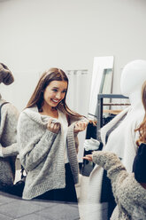 Happy young woman tying on cardigan in a boutique - CHAF001334