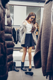 Young woman shopping for shoes in a boutique - CHAF001338